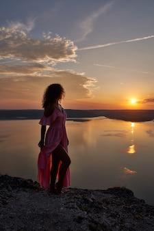 湖の近くの夕日を背景にドレスを着てポーズをとるモデル