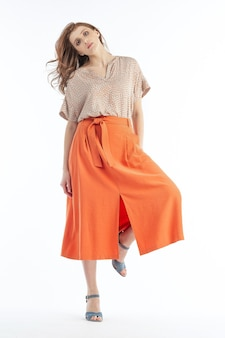 Model posing for picture in the light blouse and orange skirt