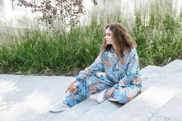 옷 카탈로그의 새로운 컬렉션에서 계단에 앉아 포즈를 취하는 모델