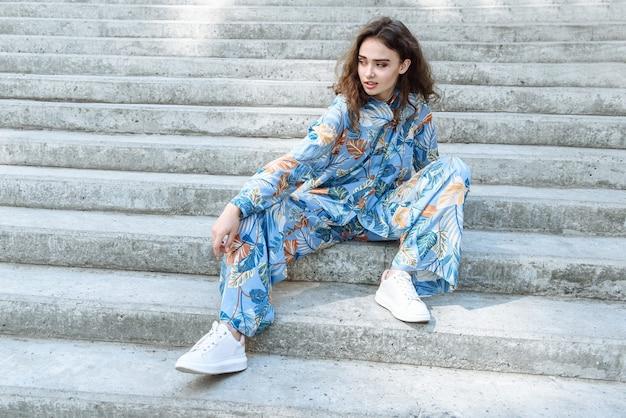 도시 의류 카탈로그 야외 계단에 앉아 포즈를 취하는 모델