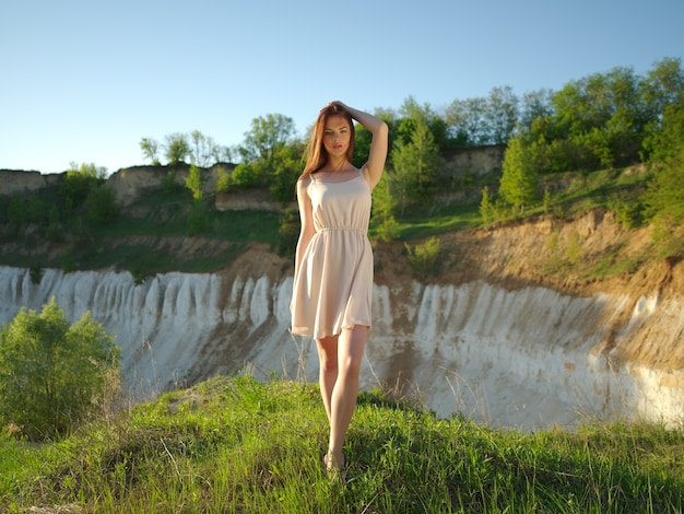 Model posing on a sunny day with a great sunny landscape around her. young woman standing by a cliff with a nice view behind he back. attractive girl with a white dress posing outdoors.