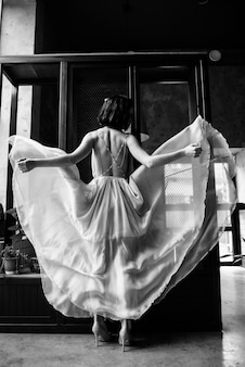 Model posing in a white long wedding dress indoors by the window.