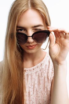 Model posing with glasses on white wall