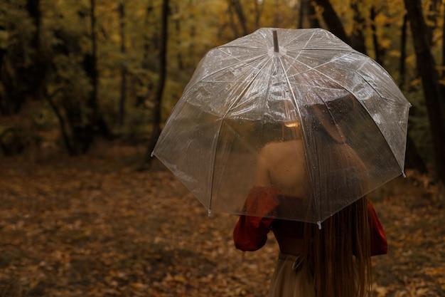 暗い背景に秋の透明な傘でモデルの背面図。秋のブログ