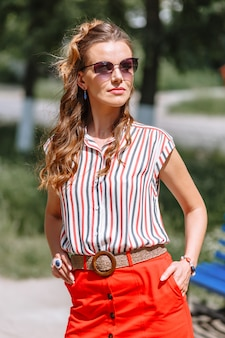 Model in a red skirt and striped blouse on the street