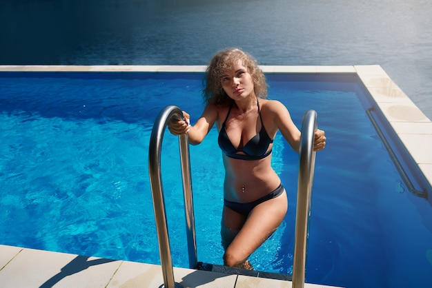 Model resting in pool outdoors