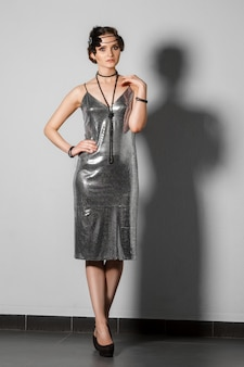 Model in retro style silver tinsel dress with plume in hair