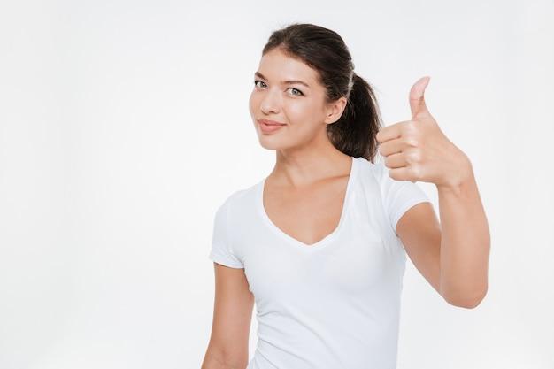 Модель показывает палец вверх в студии изолированной белой стене