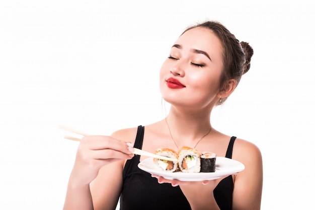 Model shows pleasure after having sushi rolls meal holding chopsticks