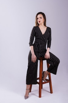 Model sits on a chair on a gray background. office jumpsuit