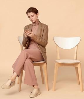 Модель сидит рядом с пустым стулом