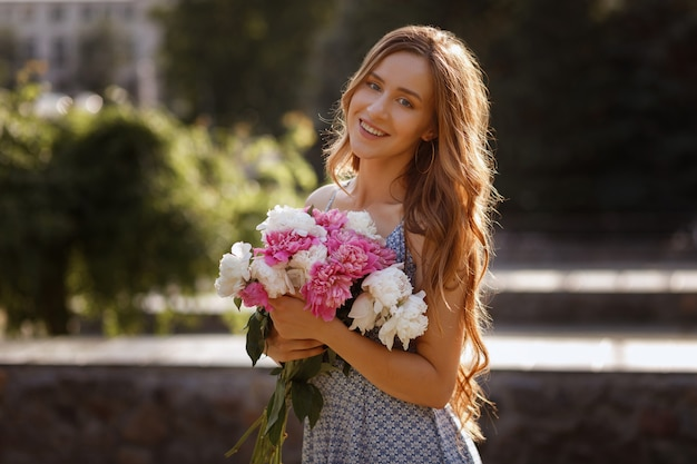 The model smiles and holds in her hands a bouquet of peonies flowers. sunset in the city for a walk.