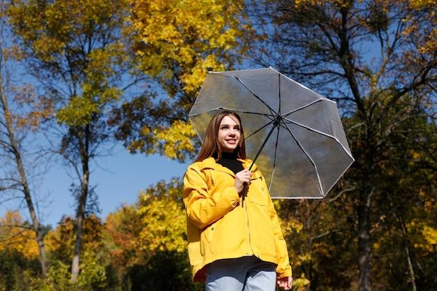 Модель улыбается в желтом плаще с зонтиком в солнечный осенний день