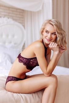 침실에서 섹시한 레이스 속옷을 입고 포즈를 취하는 동안 웃는 모델