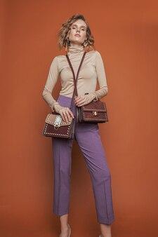 モデルはベージュのポロネックと紫のズボンを着て2つのバッグを抱えています。