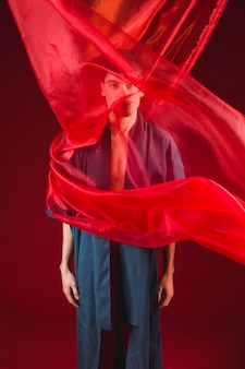 Model standing and posing with red cloth