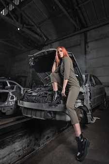 Model in stylish clothes  sitting on open hood in disassembled car in the garage.