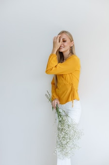 Model in stylish clothes with flowers in hand on a monochromatic background. image for autumn