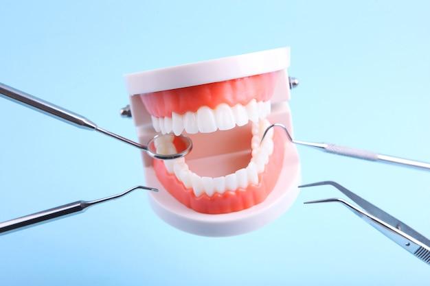 Модели зубов и стоматологические инструменты парят в воздухе на синем фоне
