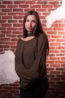 自然なメイクでかなりブルネットのモデルのモデルテスト、レンガの壁の背景にポーズをとって、特大のセーターを着ています
