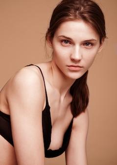 Модельный портрет испытания при молодая красивая фотомодель представляя на серой предпосылке. черный бюстгальтер