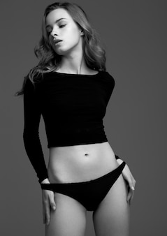 Model test with young beautiful fashion model wearing black t-shirt and panties in studio.black and white