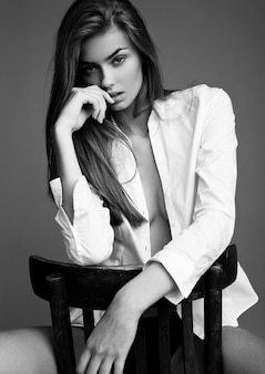 Model test with young beautiful fashion model wearing white shirt sitting on chair