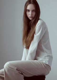 Модельный тест с молодой красивой фотомоделью с длинными волосами в белой рубашке на сером фоне