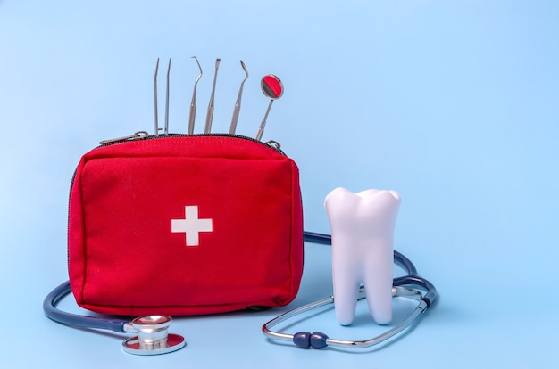 A model of a tooth a stethoscope a dental instrument a first aid kit