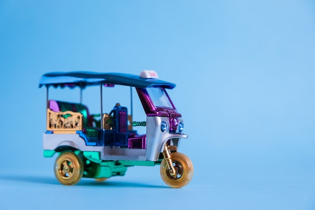 Model toy tuk tuk isolated on blue wall. thai traditional taxi in bangkok thailand. souvenir