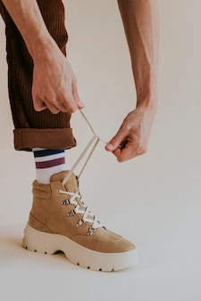 Модель завязывает шнурки на замшевых кроссовках