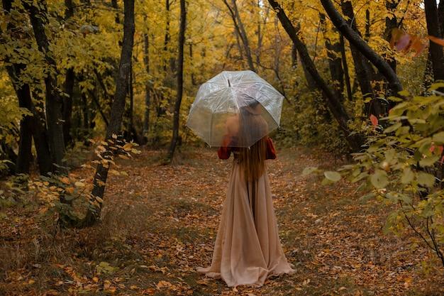 公園で傘の雨の秋のモデルビュー。ポスター。ハロウィーン