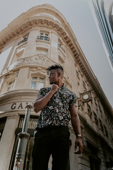 Model in vintage shirt posing in front of a beautiful building