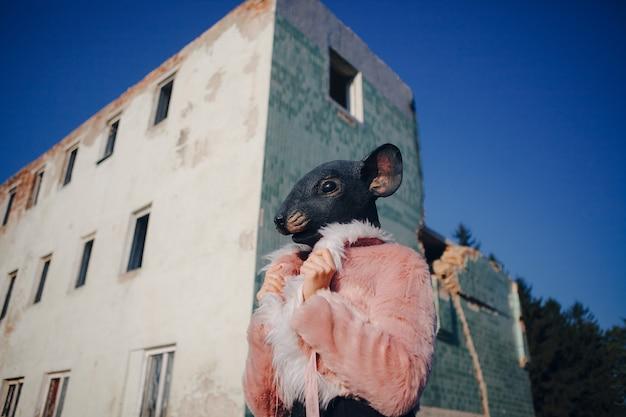 Модель в маске мышки позирует в розовой шубе