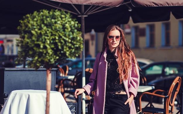 Model wearing stylish coat and sunglasses