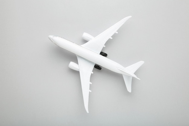 Model white airplane on a grey background. travel concept