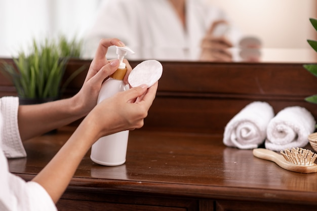 A model in a white bathrobe squeezes a product from a white bottle, which stands on a brown wooden dressing table, on which towels, a comb and a flower pot stand, on a cotton pad. close-up.