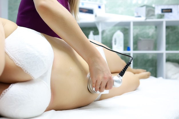 A model in a white bra and white panties is lying on the procedure with a massage master, he gives her an ultrasound massage, thus breaking up cellulite