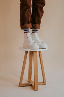 Model in white high top sneakers standing on chair
