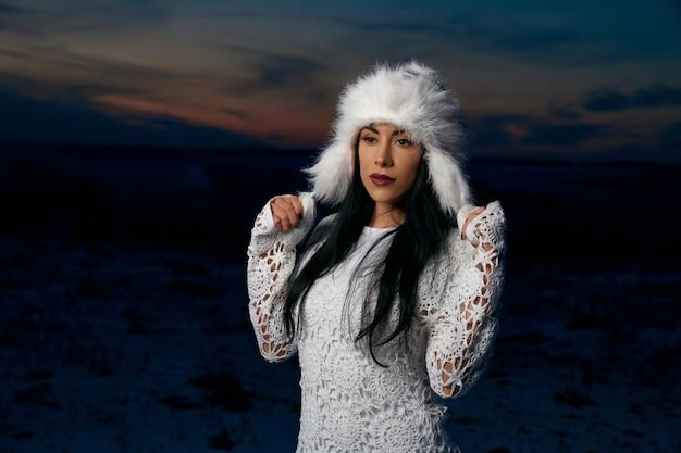 Model in winter hat in field with snow.