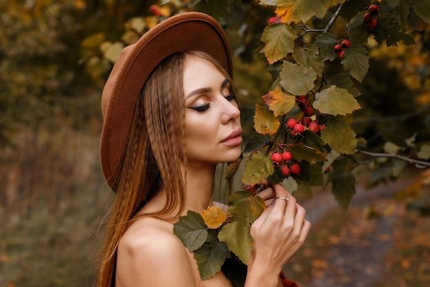 山の灰の近くに秋の化粧をしたモデル。閉じる。ポスター