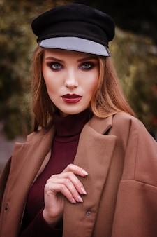 Модель с красивым осенним макияжем в кепке и стильном образе