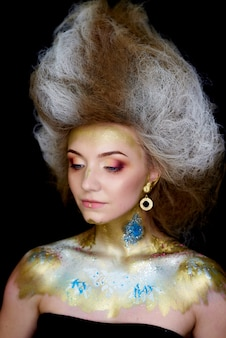 Model with beautiful blue eyes with makeup, hairstyle and body art on a black .