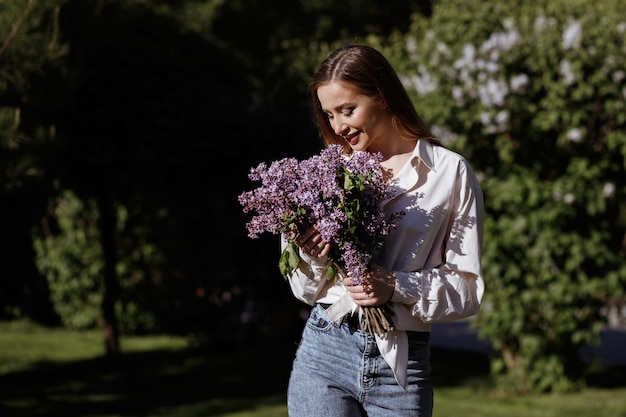 Model with a bouquet of lilacs for a walk in the park. summer walk in the park. blurred green space. smile and happiness