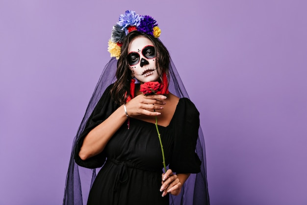 Model with brown eyes with face art of skull and in black veil demonstrating red rose. girl posing confidently on isolated wall.