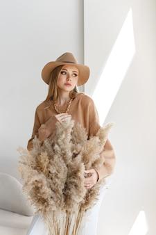 スタジオで乾いた草のメイクと秋の服を着たモデル