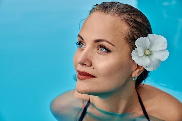 スイミングプールの髪に花を持つモデル。