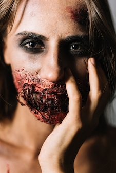 Model with halloween makeup touching face