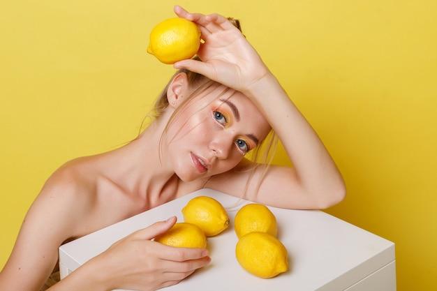 노란색 벽에 레몬 모델 프리미엄 사진