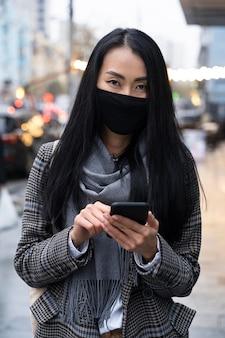 Modello con maschera che tiene smartphone